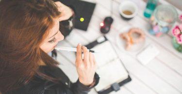 Schlusssatz der Bewerbung - Frau nachdenklich über dem Schreibtisch