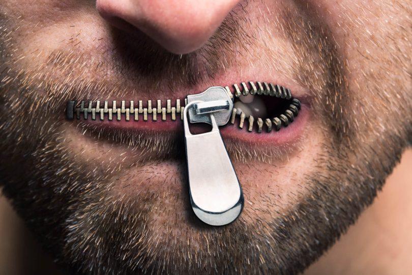 Sperrvermerk - Bitte um Vertraulichkeit: Mann mit Reißverschluss als Mund