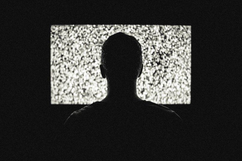 Mann vor einem Fernseher