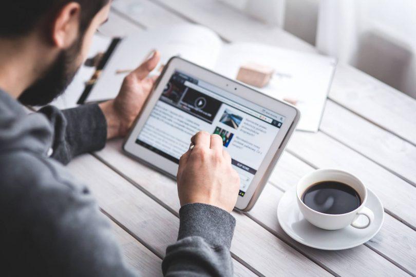 Informationen über die Unternehmen: Mann recherchiert am Tablet