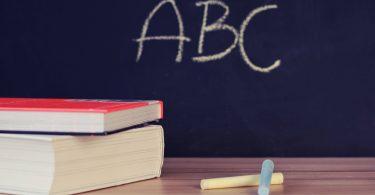 Rechtschreibung und Grammatik: Schulbücher vor einer Tafel