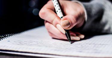 Berufsbegleitendes Studium: Schreibende Hand auf einem Notizbuch