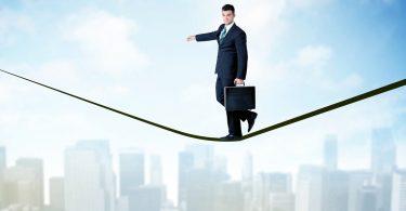 Fehlende fachliche Qualifikation ausgleichen: Mann balanciert im Anzug auf einem Seil