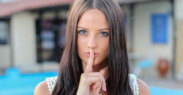 Gründe für Ihre Jobsuche verschweigen: Frau mit Finger auf den Lippe