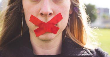 Gründe für Ihre Jobsuche verschweigen 2: Frau mit rotem Klebeband über den Lippen