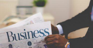 Stellensuche in Zeitungen und Zeitschriften: Mann klappt Business-Zeitung auf