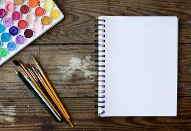 Gestaltung vom Bewerbungsflyer: ein Farbkasten, mehrere Pinsel und ein Block liegen auf einem Holztisch.