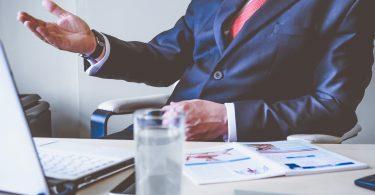 Personaler sitzt im Anzug beim Vorstellungsgespräch am Tisch und gestikuliert