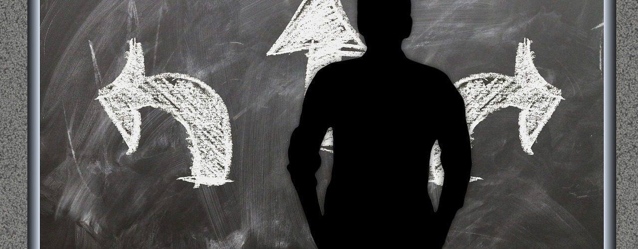Mann steht vor einer Tafel mit drei Pfeilen in verschiedenen Richtungen