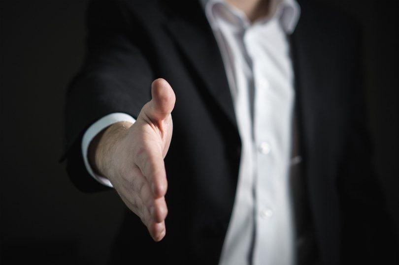 Mann streckt Hand bei Verabschiedung von Vorstellungsgespräch heraus