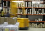 Regal in einer Lagerhalle mit vorbeifahrendem Gabelstapler (Logistik)