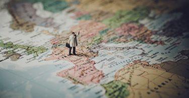 Miniaturfigur mit Aktentasche steht auf einer Weltkarte (Praktikum im Ausland)