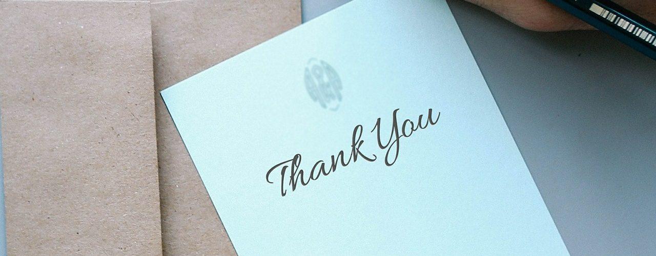 Dankschreiben mit Hand und Stift daneben